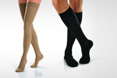 Caregiver helps somebody putting anti-thrombotic stockings on